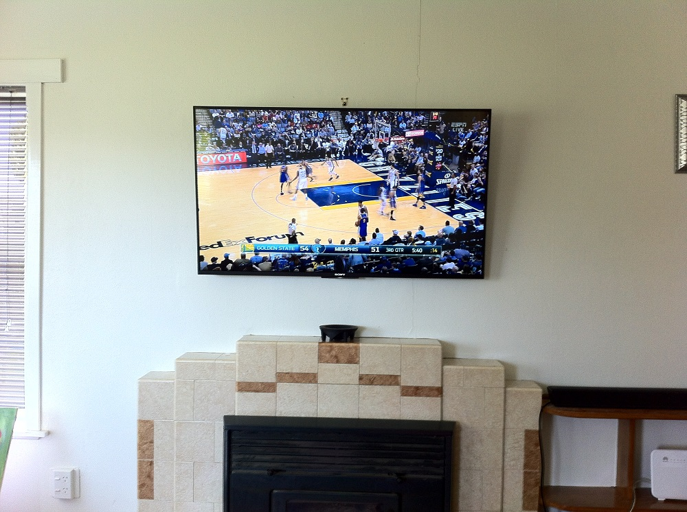 tv mounted above a fireplace in glen innes
