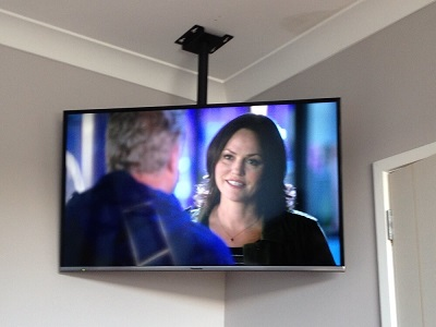the wow factor of a ceiling mounted tv in the corner of a bedroom wall