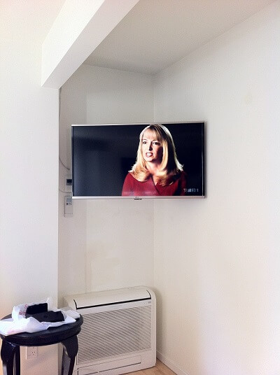 swivel mounted tv in a corner of a wall